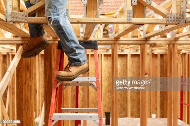 legs of black man on ladder at construction site - work shoe stock-fotos und bilder