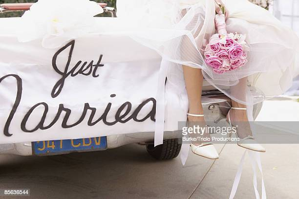 Legs of bride on car with just married sign