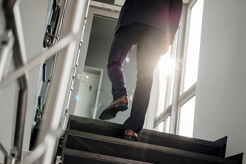 Legs of businessman walking upstairs - gettyimageskorea