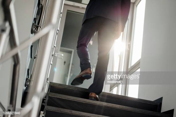 legs of businessman walking upstairs - stufen stock-fotos und bilder