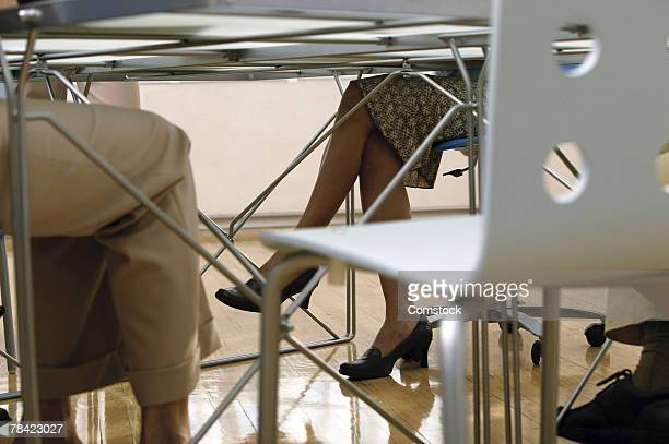 legs of businesspeople under table during meeting - under skirt stock photos and pictures