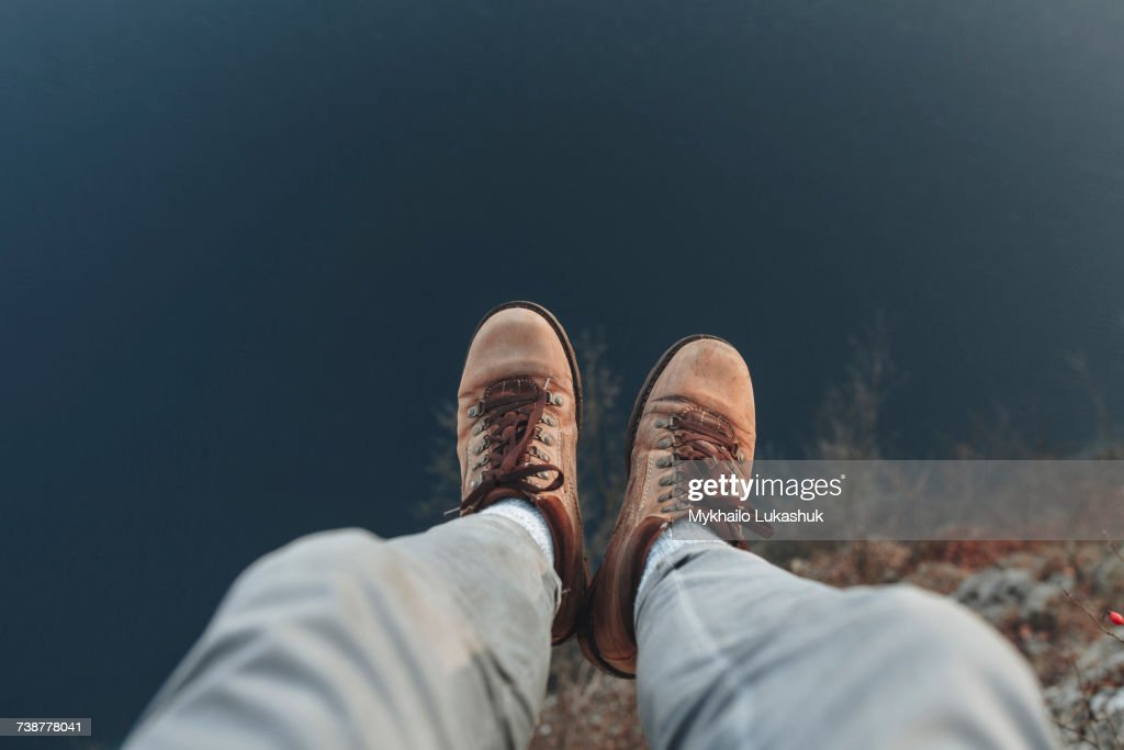 Legs of Caucasian man sitting at the edge of reservoir : Stock Photo