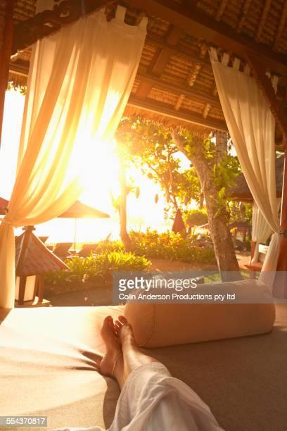 Legs of caucasian woman relaxing in cabana