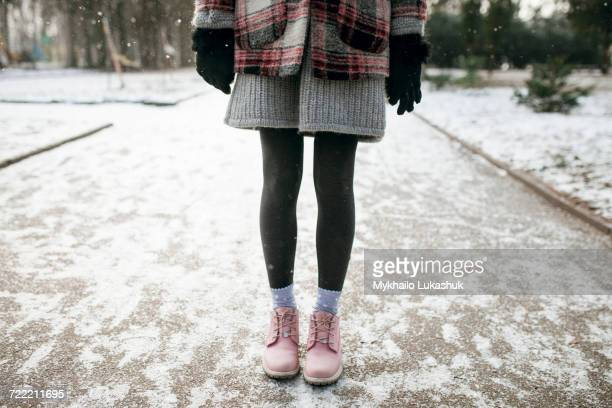 legs of caucasian woman standing in snow - stiefel stock-fotos und bilder