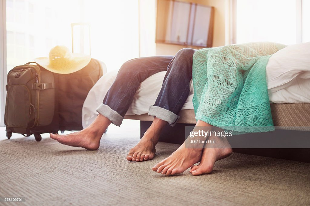 Legs of couple laying on bed in hotel room : Stock Photo