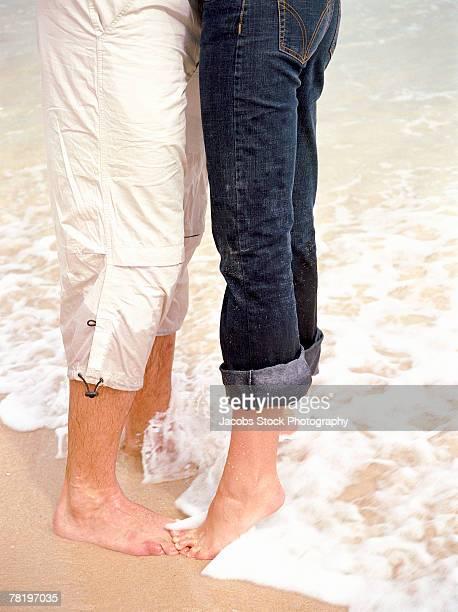 Legs of couple on beach