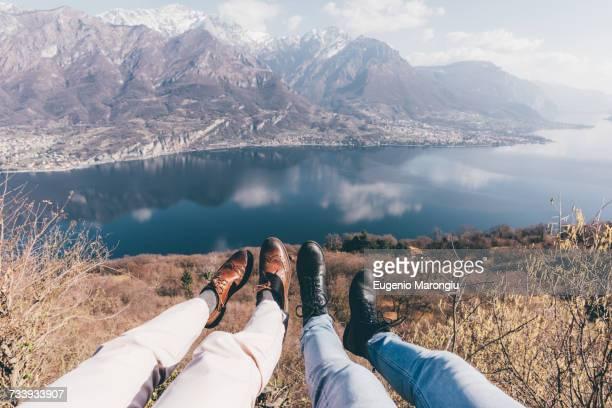 Legs of couple over mountain lakeside, Monte San Primo, Italy