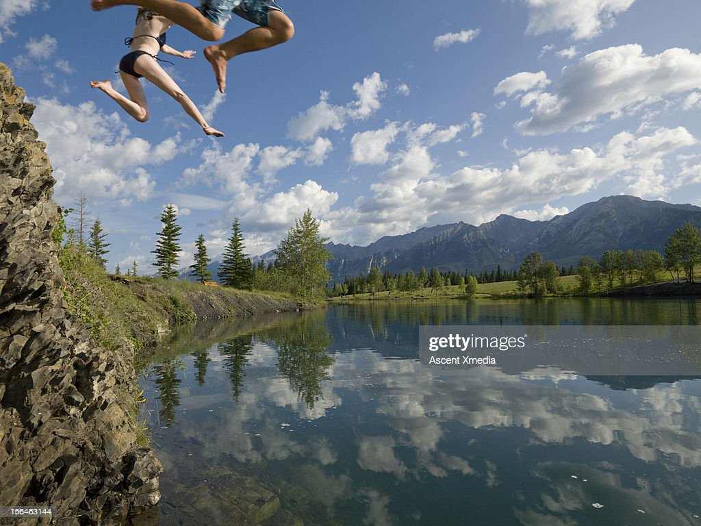 Legs of couple plunging towards a mountain lake : Stock Photo
