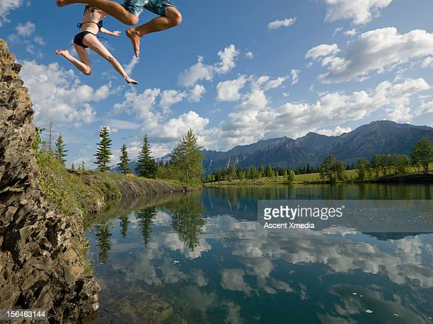 legs of couple plunging towards a mountain lake - taking the plunge stock photos and pictures