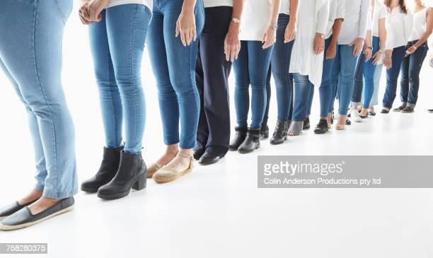 Legs of diverse women waiting in long line