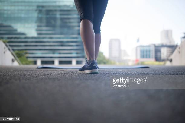 Legs of female athlete next to gymnastics mat in the city