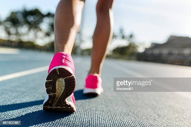 Legs of female athlete running on racetrack