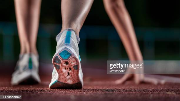 legs of female athlete running on tartan track - athleticism stock pictures, royalty-free photos & images