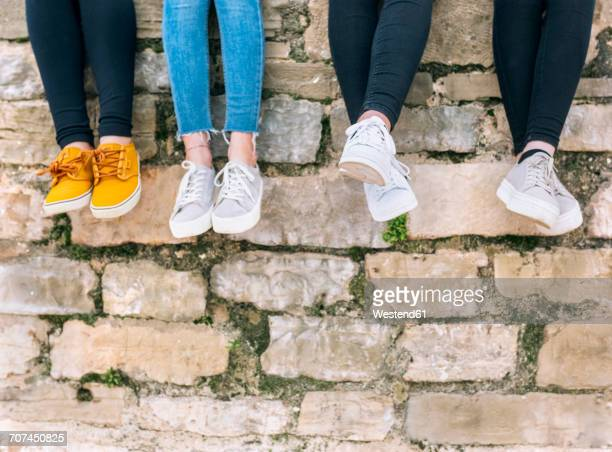 Legs of four friends sitting side by side on a wall