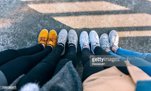 Legs of four friends standing side by side