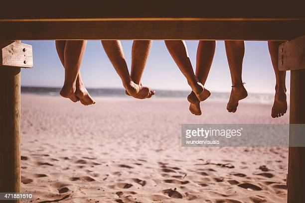 Legs of friends sitting on a beach boardwalk together