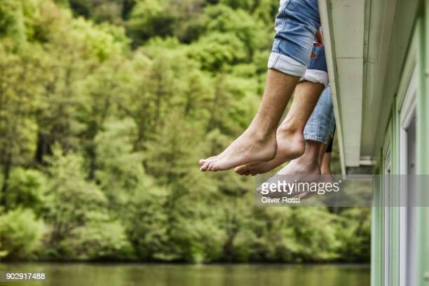 legs of friends sitting on a houseboat - mujeres fotos stock pictures, royalty-free photos & images
