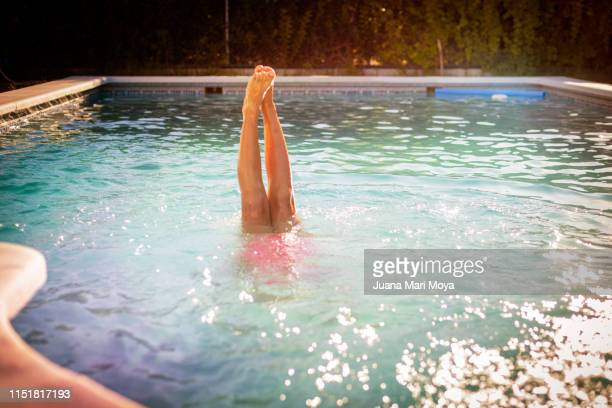 legs of girl coming out of a pool.  it's doing the pine - playing footsie stock pictures, royalty-free photos & images
