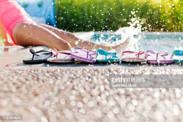 legs of girls making a splash in a pool, with flip-flops in the foreground - flip flop stock pictures, royalty-free photos & images