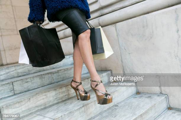 Legs of glamorous woman carrying shopping bags on staircase