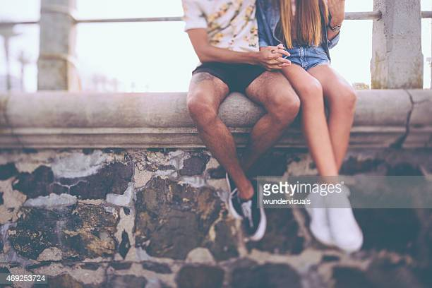 Legs of hipster couple sitting on a wall holding hands