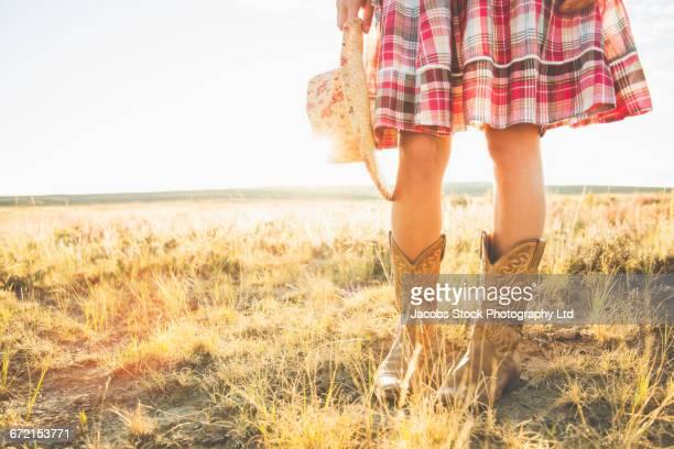 legs of hispanic woman wearing cowboy boots holding hat in desert - カウボーイブーツ ストックフォトと画像