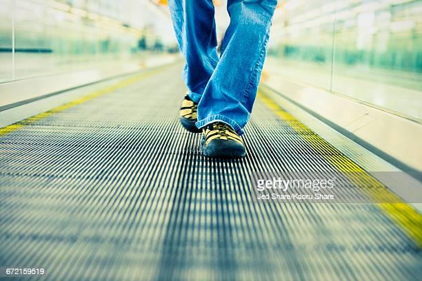 Legs of Japanese woman wearing jeans walking on moving walkway