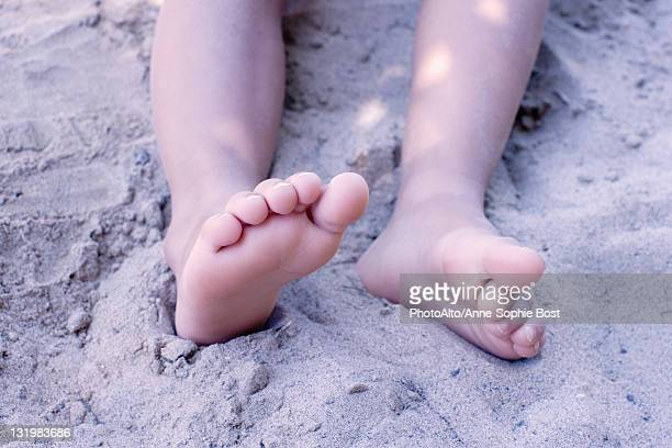 Legs of little girl in sand, low section