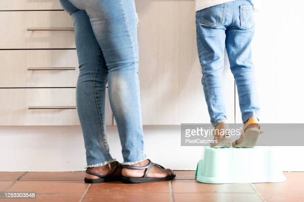 legs of little girl standing on booster step next to mother at the kitchen counter - low section stock pictures, royalty-free photos & images
