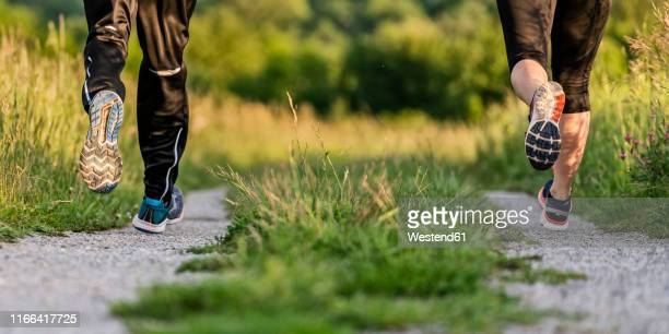 legs of man and woman jogging - sportkleidung stock-fotos und bilder