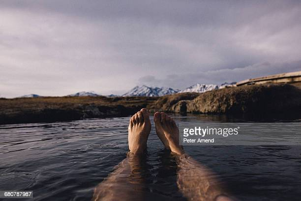 legs of man floating in water on lake, mammoth lakes, california, usa - mujeres fotos stock pictures, royalty-free photos & images