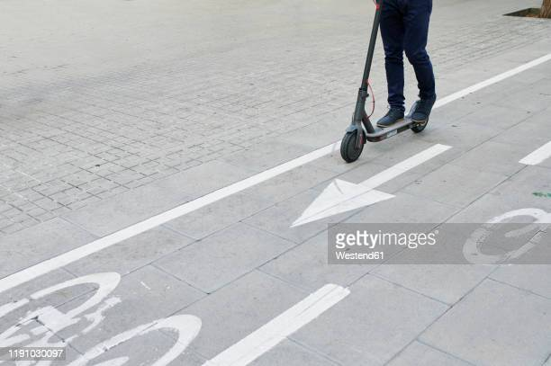 legs of man riding e-scooter on bicycle lane in the city - %e... ストックフォトと画像
