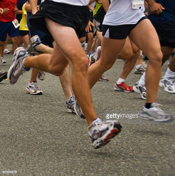 Legs of many runners are shown at the start of a 10K