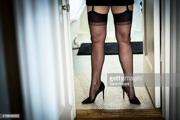 legs of mature woman in doorway wearing stockings and high heels - women in stockings and high heels stock photos and pictures