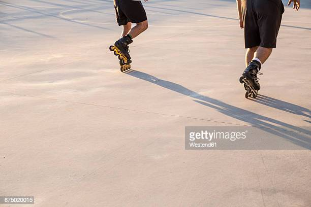 Legs of men with rollerblades skating