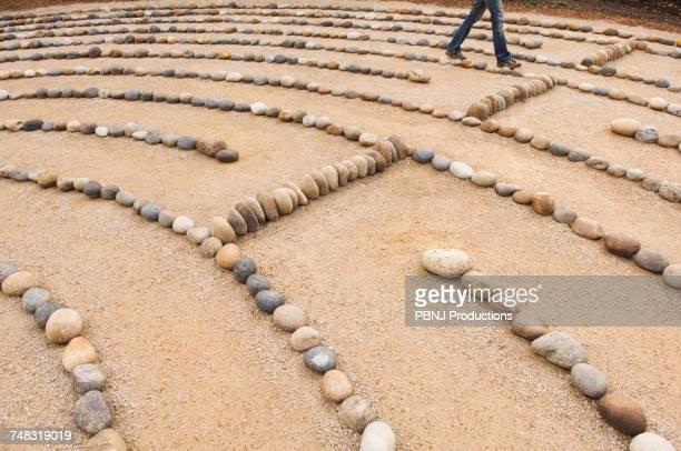 legs of Mixed Race woman walking in maze