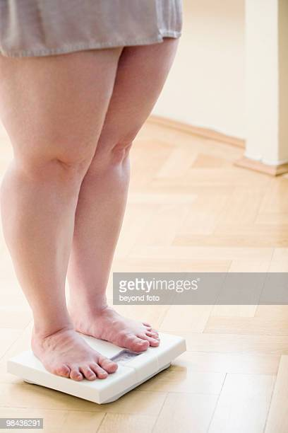 legs of overweight woman checking her weight on bathroom scales - chubby legs stock photos and pictures