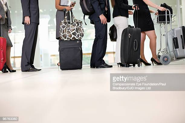 legs of people waiting in airport line up