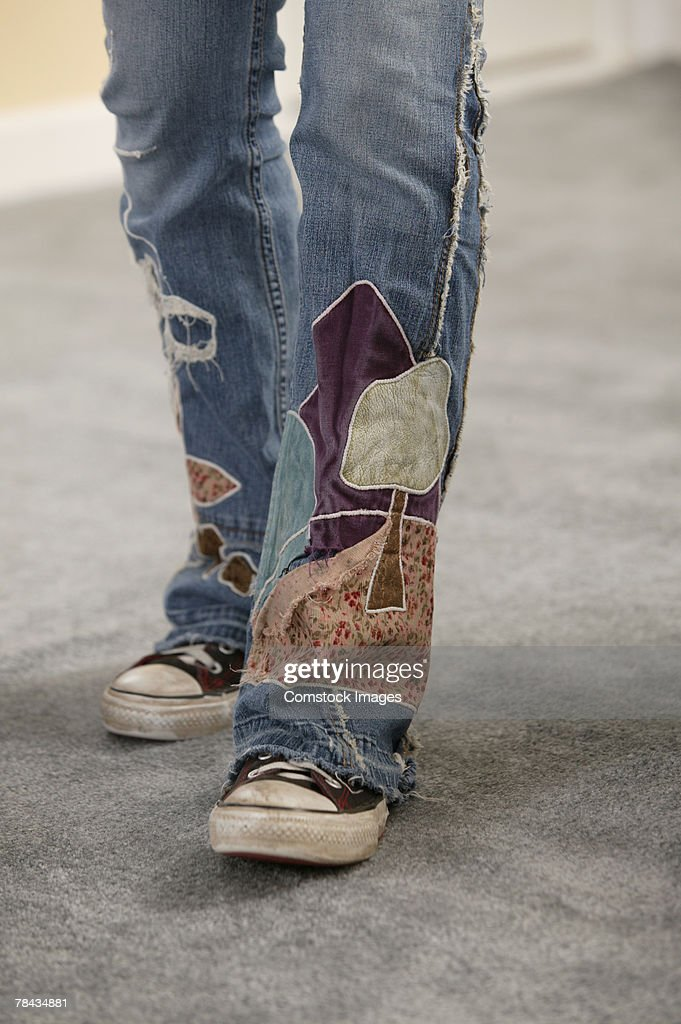 Legs of person wearing jeans with patches : Stockfoto