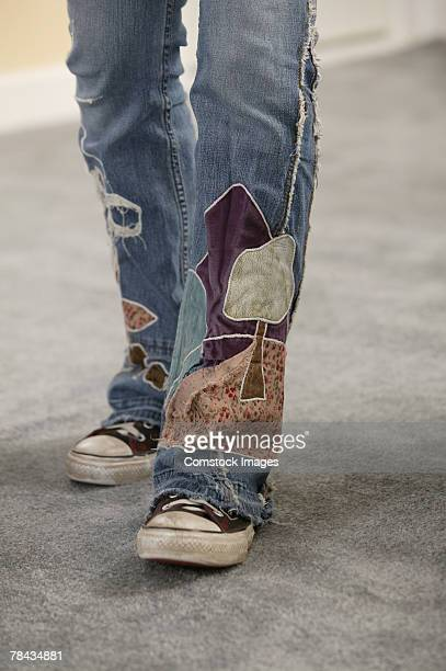 legs of person wearing jeans with patches - つぎあて ストックフォトと画像