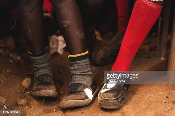 legs of poor african children, with dirty shoes and red socks, in a classroom without a floor - black shoe stock pictures, royalty-free photos & images