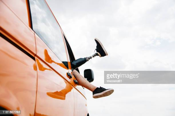 legs of prosthetic young man dangling out of camper van window - amputiert stock-fotos und bilder