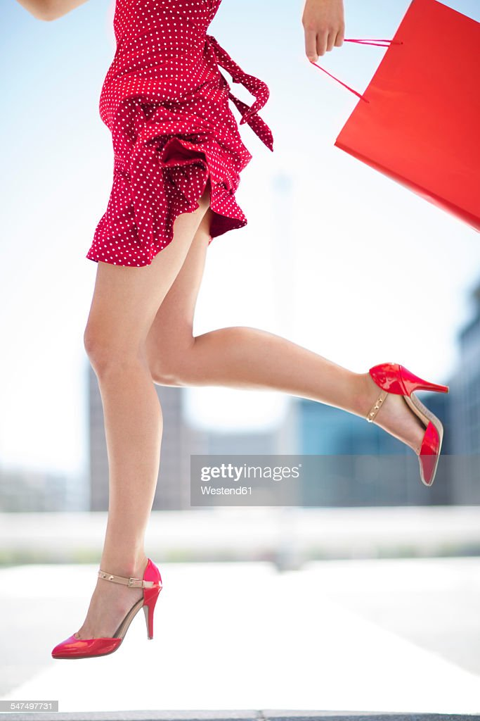 Legs of red dressed woman with shopping bag : Stock Photo