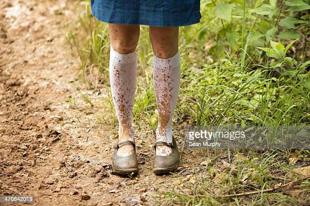 legs of schoolgirl on muddy path. - ハイソックス ストックフォトと画像