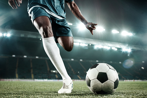Legs of soccer player kicking the ball 1129575516