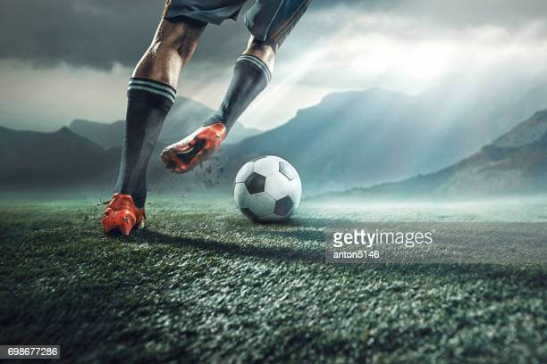 legs of soccer player kicking the ball - calcio di squadra foto e immagini stock