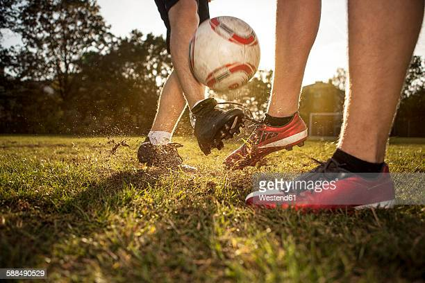 Legs of soccer players on soccer pitch
