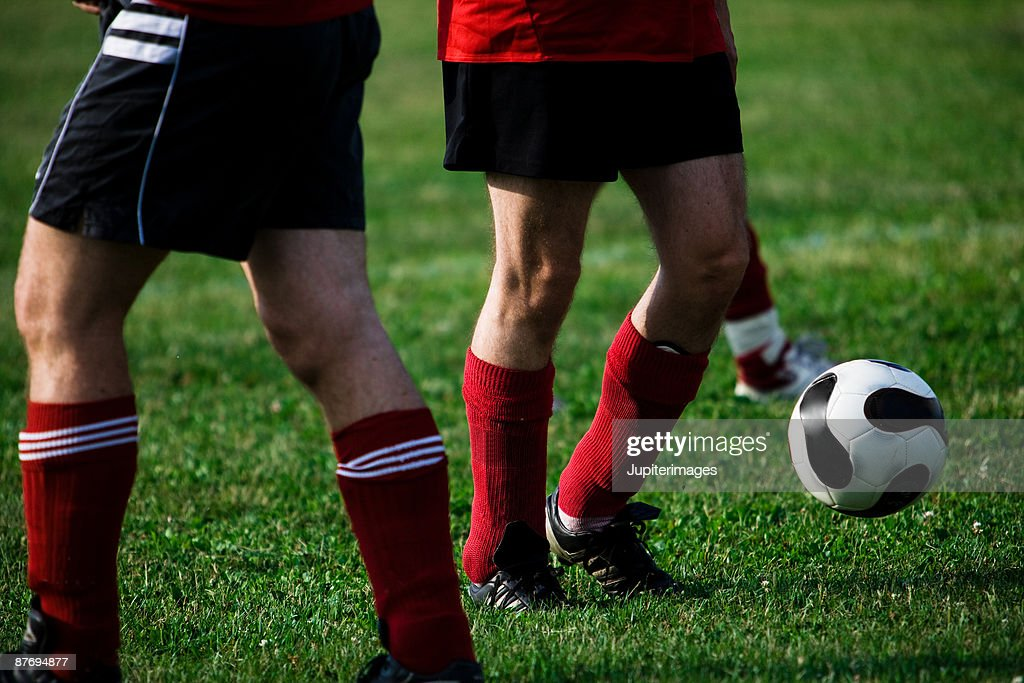 Legs of soccer players with ball : Stock Photo