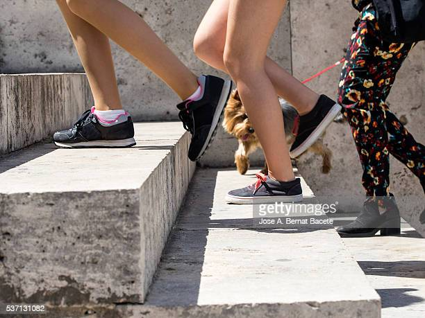 Legs of teen children in shorts and of a woman raising a few stairs outdoors