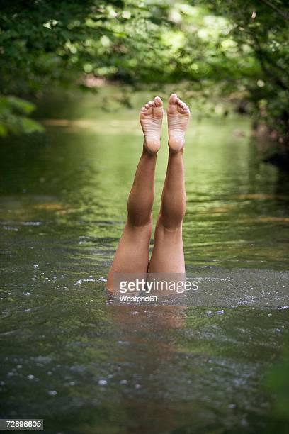 Legs of teenage girl (13-15) in river